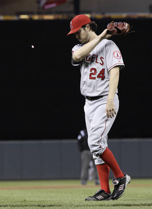 Photo -   Los Angeles Angels pitcher Dan Haren, right, swats his bubble gum with his glove as he leaves the game in the fourth inning of a baseball game against the Minnesota Twins Tuesday, May 8, 2012, in Minneapolis. Haren gave up eight hits and five runs in three-and-two-thirds innings. (AP Photo/Jim Mone)