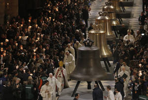 Photo - Some of the nine new bronze bells are displayed in Notre Dame cathedral during a ceremony of blessing by Paris Archbishop Andre Vingt-Trois in Paris, Saturday, Feb. 1, 2013. Nine enormous new bronze bells have made their way at Notre Dame Cathedral, helping the medieval edifice to rediscover its historical harmony. (AP Photo/Francois Mori)