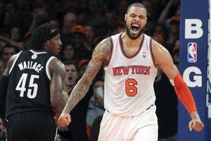 Photo - Brooklyn Nets' Gerald Wallace (45) watches as New York Knicks' Tyson Chandler (6) reacts after dunking during the second half of an NBA basketball game, Wednesday, Dec. 19, 2012, at Madison Square Garden in New York. The Knicks won 100-86. (AP Photo/Mary Altaffer)