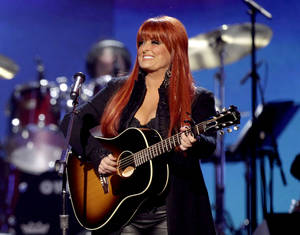 Photo -   FILE - This April 4, 2011 file photo shows country winger Wynonna Judd from The Judds, performing at the Girls' Night Out: Superstar Women of Country in Las Vegas. Judd says she is postponing scheduled concerts in Canada next week after her husband was hurt in a motorcycling accident in South Dakota, Saturday, Aug. 19, 2012. (AP Photo/Julie Jacobson, file)