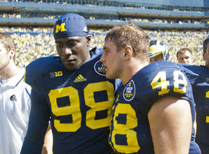 Photo - Michigan quarterback Devin Gardner (98) has words with linebacker Desmond Morgan (48) after an NCAA college football game against Akrain in Ann Arbor, Mich., Saturday, Sept. 14, 2013. Michigan won 28-24. Gardner had 3 interceptions and 1 lost fumble. (AP Photo/Tony Ding)
