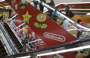 Photo - In this photo taken Sunday, Dec. 15, 2013, shoppers take escalators under the logo of Nintendo and Super Mario characters at an electronics store in Tokyo. This holiday season Nintendo faces a critical test with its Wii U video game console that is pitted against Sony's PlayStation 4 and Microsoft's Xbox One as it seeks to revive flagging sales. (AP Photo/Shizuo Kambayashi)