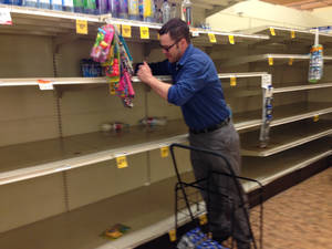 Photo - Matt Smith purchases some of the last bottled water available Friday, May 23, 2014 at a Safeway store in Portland, Ore. A citywide boil notice was issued Friday for Portland, after E. coli was detected in the water supply, causing a rush on bottled water. (AP Photo/Gosia Wozniacki)