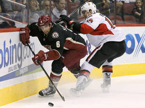 Photo - Phoenix Coyotes' David Schlemko (6) tries to keep the puck away from Ottawa Senators' Colin Greening (14) during the first period in an NHL hockey game Tuesday, Oct. 15, 2013, in Glendale, Ariz. (AP Photo/Ross D. Franklin)
