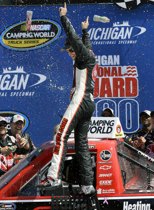 Photo - James Buescher celebrates winning the NASCAR Camping World Truck series Michigan National Guard 200 auto race at Michigan International Speedway in Brooklyn, Mich., Saturday, Aug. 17, 2013. (AP Photo/Paul Sancya)