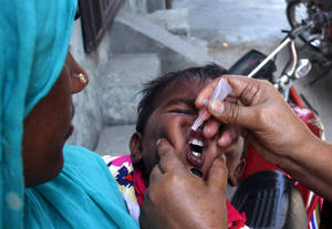 Photo - A Pakistani health worker gives a child a polio vaccine in Lahore, Pakistan, Monday, May 5, 2014. For the first time, the World Health Organization on Monday declared the spread of polio an international public health emergency that could grow in the next few months and unravel the nearly three-decade effort to eradicate the crippling disease. (AP Photo/K.M. Chaudary)