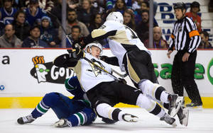 Photo - Pittsburgh Penguins' Olli Maatta, center, of Finland, and Brandon Sutter, right, and Vancouver Canucks' Jannik Hansen, left, of Denmark, collide during the first period of an NHL hockey game Tuesday, Jan. 7, 2014, in Vancouver, British Columbia. (AP Photo/The Canadian Press, Darryl Dyck)