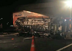 Photo - In this image from video the limousine bus carrying Tracy Morgan and six other people lies on it's side early Saturday morning, June 7, 2014, on the New Jersey Turnpike. A New Jersey highway crash that severely injured Tracy Morgan and killed another comedian is drawing attention to the dangers of tired truckers just as the industry and its allies in Congress are poised to roll back safety rules on drivers' work schedules.  (AP Photo/Will Vaultz Photography)