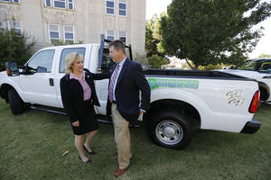 Photo - Gov. Mary Fallin and Cleveland County Commissioner Rod Cleveland on Thursday discuss the two new CNG trucks Cleveland County recently purchased in Norman. Photo By Steve Gooch, The Oklahoman <strong>Steve Gooch</strong>