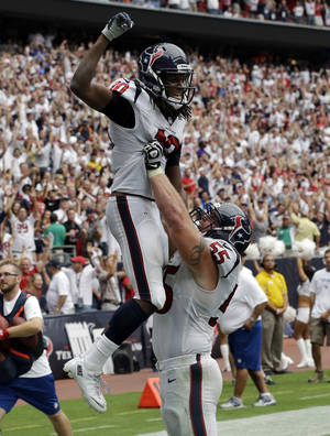 Photo - Houston Texans' DeAndre Hopkins (10) is lifted by teammate Chris Myers after scoring the winning touchdown against the Tennessee Titans during overtime of an NFL football game on Sunday, Sept. 15, 2013, in Houston. (AP Photo/David J. Phillip)