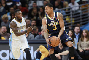 Photo - Utah Jazz guard Trey Burke, right, pulls in a loose ball as Denver Nuggets guard Nate Robinson comes in to cover in the first quarter of an NBA basketball game in Denver on Friday, Dec. 13, 2013. (AP Photo/David Zalubowski)
