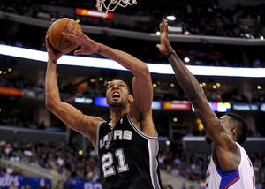 Photo - San Antonio Spurs forward Tim Duncan (21) gets by Los Angeles Clippers center DeAndre Jordan (6) for a basket in the first half of a NBA basketball game, Tuesday, Feb. 18, 2014, in Los Angeles.(AP Photo/Gus Ruelas)