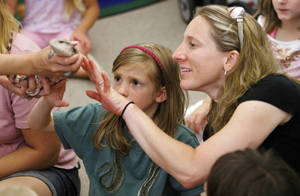 Photo - Rebecca Conrad, 8, and her mother, Nancy Conrad, touch a blue-tongued skink, a reptile from Australia, during the Awesome Australia program Monday night at the Choctaw Library.