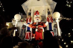 "photo - This Dec. 4, 2012 photo shows spectators viewing a a giant Santa Claus at a decorated home in the Brooklyn borough of New York. Each holiday season, tour operator Tony Muia takes tourists from around the world on his ""Christmas Lights & Cannoli Tour"" visiting the Brooklyn neighborhoods of Dyker Heights and Bay Ridge, where locals take pride in over-the-top holiday light displays.  (AP Photo/Seth Wenig)"