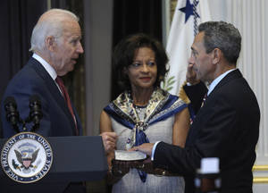 Photo - Vice President Joe Biden administers the oath of office to Mel Watt as director of the Federal Housing Finance Agency during a ceremonially swearing-in ceremony, Monday, Jan. 6, 2014, in the Eisenhower Executive Office Building on the White House complex in Washington. Watt's wife, Eulada Watt watches at center. (AP Photo/Susan Walsh)