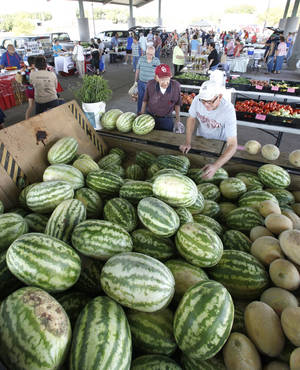 Photo - Shoppers look through Oklahoma-grown watermelons and cantaloupe at a recent Farmers Market at Festival Market Place in downtown Edmond.