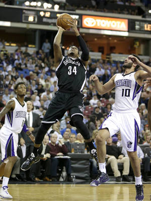 Photo - Brooklyn Nets forward Paul Pierce, center, drives between Sacramento Kings' Ben McLemore, left, and Greivis Vasquez, of Venezuela, during the first quarter of an NBA basketball game in Sacramento, Calif., Wednesday, Nov. 13, 2013. (AP Photo/Rich Pedroncelli)