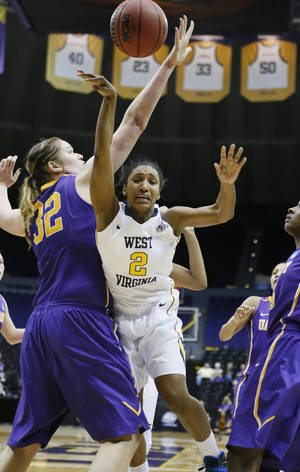 Photo - West Virginia guard Taylor Palmer (2) goes airborne after being fouled by Albany center Megan Craig (32) in the second half of an NCAA college basketball first-round tournament game on Sunday, March 23, 2014, in Baton Rouge, La. West Virginia won 76-61. (AP Photo/Rogelio V. Solis)