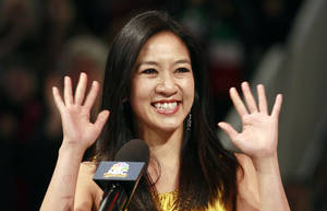 Photo - FILE - In this Jan. 28, 2012 file photo, former figure skater Michelle Kwan waves at an on-ice recognition for her Hall of Fame induction at the U.S. Figure Skating Championships in San Jose, Calif. Kwan is fitting in some time for political campaigning while she covers the Sochi Games. The two-time Olympic figure skating medalist is asking notable names to pose for a photo holding a pin supporting Clay Pell for governor of Rhode Island. Her husband announced Jan. 27, 2014, that he is running for the state's top office. (AP Photo/Jeff Chiu, File)