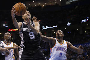 Photo - San Antonio Spurs guard Tony Parker (9) shoots in front of Oklahoma City Thunder forward Serge Ibaka (9) and center Kendrick Perkins during the third quarter of an NBA basketball game in Oklahoma City, Thursday, April 3, 2014. Oklahoma City won 106-94. (AP Photo/Sue Ogrocki)