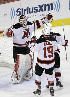 photo -   New Jersey Devils&#039; Martin Brodeur, Travis Zajac and Andy Greene. from left, celebrate after the Devils won Game 5 of a second-round NHL hockey Stanley Cup playoff series against the Philadelphia Flyers, Tuesday, May 8, 2012, in Philadelphia. New Jersey won 3-1 and won the series 4-1. (AP Photo/Matt Slocum)  