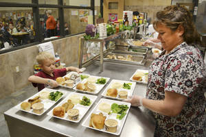 photo - Kay Rainwater watches as Jayden Drake picks up his school lunch. Photo by Zeke Campfield, The Oklahoman archives