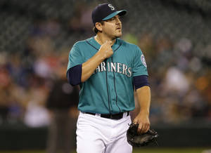 Photo - Seattle Mariners starting pitcher Joe Saunders reacts in the first inning of a baseball game after giving up a two-run single to Texas Rangers' Alex Rios in the first inning of a baseball game, Monday, Aug. 26, 2013, in Seattle. The Rangers beat the Mariners, 8-3. (AP Photo/Ted S. Warren)