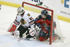 Photo - Florida Panthers' Jonathan Hueberdeau (11) slides into the goal and watches game action with Chicago Blackhawks' goalie Corey Crawford (50) during the second period of an NHL hockey game in Sunrise, Fla., Tuesday, Oct. 22, 2013. (AP Photo/J Pat Carter)