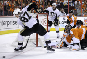 Photo - Philadelphia Flyers goalie Ilya Bryzgalov, of Russia (30) watches as Pittsburgh Penguins' Sidney Crosby (87) tries to control the puck during the first period of an NHL hockey game Saturday, Jan.19, 2013, in Philadelphia. (AP Photo/Mel Evans)