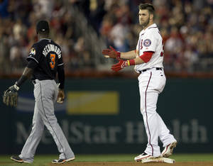 Photo - Washington Nationals left fielder Bryce Harper, right, claps after doubling to right center, allowing Jayson Werth to score in the sixth inning of a baseball game at Nationals Park in Washington, on Friday, Sept. 20, 2013. (AP Photo/Jacquelyn Martin)