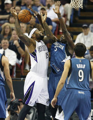Photo - Sacramento Kings center DeMarcus Cousins (15) battles under the basket against Minnesota Timberwolves Gorgui Dieng (5) during the first half of an NBA basketball game in Sacramento, Calif., on Sunday, April 13, 2014.(AP Photo/Steve Yeater)