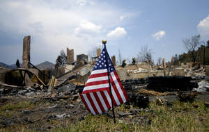 Photo - A United States flag is planted near one of the homes destroyed by the Waldo Canyon Fire in the Mountain Shadows neighborhood of Colorado Springs, Colo., on Monday, July 2, 2012. So far, the blaze, now 45 percent contained, has damaged or destroyed nearly 350 homes. (AP Photo/Bryan Oller) ORG XMIT: COBO102