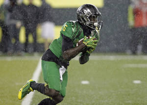 Photo - Oregon running back DeAnthony Thomas returns a punt on the first play during the first half of an NCAA college football game against California in Eugene, Ore., Saturday, Sept. 28, 2013. Thomas was injured on the play and had to be helped off the field.(AP Photo/Don Ryan)