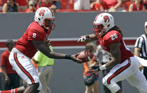 Photo - North Carolina State quarterback Brandon Mitchell (8) hands off to Tony Creecy (26) during the first half of an NCAA college football game against Louisiana Tech in Raleigh, N.C., Saturday, Aug. 31, 2013. (AP Photo/Gerry Broome)