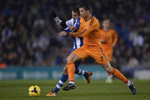 Photo - Real Madrid's Cristiano Ronaldo, right, duels for the ball against Espanyol's Christian Stuani during a Spanish La Liga soccer match at Cornella-El Prat stadium in Cornella Llobregat, Spain, Sunday, Jan. 12, 2014. (AP Photo/Manu Fernandez)