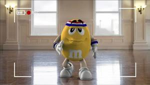 "Photo - This image provided by Mars Inc. shows an online teaser ad for M&M's Super Bowl ad featuring its yellow peanut M&M ""spokescandy"". The teaser is part of a Super Bowl ad trend: More content is being released ahead of time online in the hope that it goes viral. Advertisers are seeking to drum up excitement for their spots running during the big game, when more than 108 million people are expected to watching Feb. 2. (AP Photo/Mars Inc.)"
