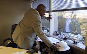 photo - Vince Fudzie, CEO of Triune,  grabs his hard hat in his office Wednesday, Dec. 12, 2012, in Dallas, Texas. Fudzie, CEO of Triune, a general contracting company based in Dallas, says business with the government has been shrinking since 2006, and the cliff presents yet another challenge. He's already been waiting to find out if he'll get approval to finish a dormitory project for the Department of Labor that's 95 percent complete.  (AP Photo/LM Otero)