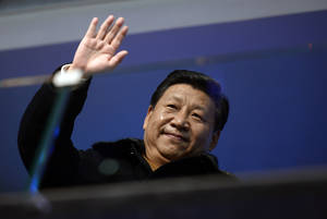 Photo - China's President Xi Jinping waves from the presidential tribune during the opening ceremony of the 2014 Winter Olympics in Sochi, Russia, Friday, Feb. 7, 2014. (AP Photo/Lionel Bonaventure, Pool)