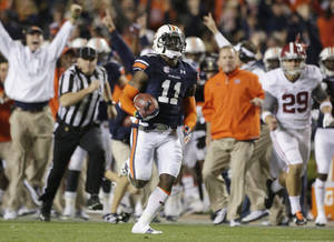 Photo - FILE - In this Nov. 30, 2013 file photo, Auburn cornerback Chris Davis (11) returns a field goal attempt 109-yards to score the winning touchdown over Alabama during the second half of an NCAA college football game in Auburn, Ala.Pursuing is punter Cody Mandell (29). Davis's 109-yard return of a missed field goal to beat Alabama was one of the Iron Bowl's and the season's most memorable plays. (AP Photo/Dave Martin, file)