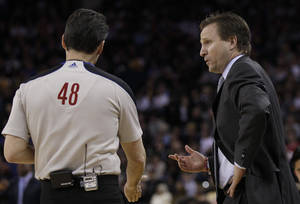 Photo - Oklahoma City Thunder head coach Scott Brooks, right, talks with referee Scott Foster (48) in the first quarter of an NBA basketball game against the Golden State Warriors in Oakland, Calif., Sunday, Feb. 13, 2011. The Warriors won 100-94. (AP Photo/Jeff Chiu)