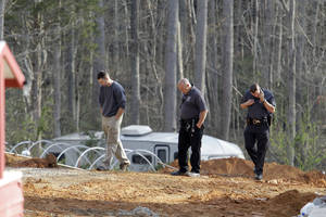 Photo - A man, left, walks with investigators Monday, April 8, 2013, around the scene of a collapsed construction site where two children died when the dirt walls collapsed Sunday on Cedarbrook Court in Stanley, N.C. (AP Photo/Bob Leverone)