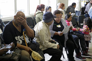 Photo - FILE - This March 31, 2014 file photo shows applicants waiting to be called during a health care enrollment event at the Bay Area Rescue Mission in Richmond, Calif. It's not too late to get covered. A few routes remain open for those who missed the health care law's big enrollment deadline. Millions may be eligible for a second chance to sign up for subsidized insurance. And people who get coverage after the deadline can still avoid, or at least reduce, the fine for going uninsured. (AP Photo/Eric Risberg, File)