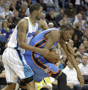 Photo - New Orleans Hornets forward Trevor Ariza, left, reaches over Oklahoma City Thunder forward Kevin Durant (35) in the second half of an NBA basketball game in New Orleans, Monday, Jan. 24, 2011. The Hornets defeated the Thunder 91-89. AP Photo
