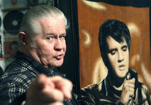 """Photo - FILE - In this Dec. 9, 2009 file photo, Paul MacLeod stands before a poster of Elvis Presley in the antebellum home and a private Elvis Presley museum he calls """"Graceland Too,"""" in Holly Springs, Miss. MacLeod, a lifetime Elvis fanatic, was found dead on the porch of his home early Thursday, July 17, 2014, two days after authorities say he shot and killed a man who forced his way into the attraction. (AP Photo/Rogelio V. Solis, File)"""