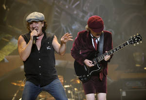 "Photo -   FILE - In this Nov. 12, 2008 file photo, AC/DC lead singer Brian Johnson, left, and Angus Young perform on the Black Ice tour at Madison Square Garden in New York. Columbia Records and Apple announced Monday, Nov. 19, 2012, that the classic rock band's music will be available at the iTunes Store worldwide. Sixteen albums will be released, including ""High Voltage"" and ""Back in Black."" (AP Photo/Jeff Zelevansky, file)"
