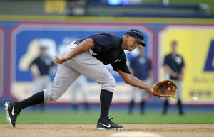 Photo - New York Yankees' Alex Rodriguez reaches for a ground ball during warm ups for a Class AA baseball game with the Trenton Thunder against the Reading Phillies, Monday, July 15, 2013, in Reading, Pa. Rodriguez is doing a rehab assignment with the Thunder recuperating from hip surgery. (AP Photo/Reading Eagle, Jeremy Drey)