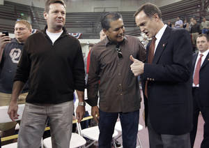 Photo - New University of Oklahoma men's basketball coach, right, talks with OU baseball coach Sunny Golloway and football coach Bob Stoops before being introduced as the new University of Oklahoma men's basketball coach on Monday, April 4, 2011, in Norman, Okla.