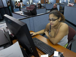 Photo -   In this Friday, Sept. 7, 2012, photo, Melina Abrey sits at a computer station, doing job applications, at WorkForce One in Hollywood, Fla. The number of Americans seeking unemployment benefits jumped to 382,000 last week, the highest level in two months. (AP Photo/J Pat Carter)