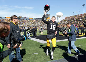 Photo - Iowa quarterback Jake Rudock (15) celebrates as he runs off the field following the team's 17-10 overtime victory over the Northwestern in an NCAA college football game Saturday, Oct. 26, 2013 at Kinnick Stadium in Iowa City, Iowa.  (AP Photo/Brian Ray)