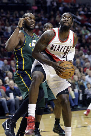 Photo - Portland Trail Blazers center J.J. Hickson, right, looks to shoot against Utah Jazz center Al Jefferson during the first quarter of an NBA basketball game in Portland, Ore., Saturday, Feb. 2, 2013.(AP Photo/Don Ryan)
